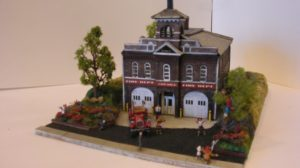 The Firehouse is built from a Laser-Art kit. This is a rare example of using a wood kit to simulate a brick structure. The fire truck is a Jordan model. By Gary Whistleman.